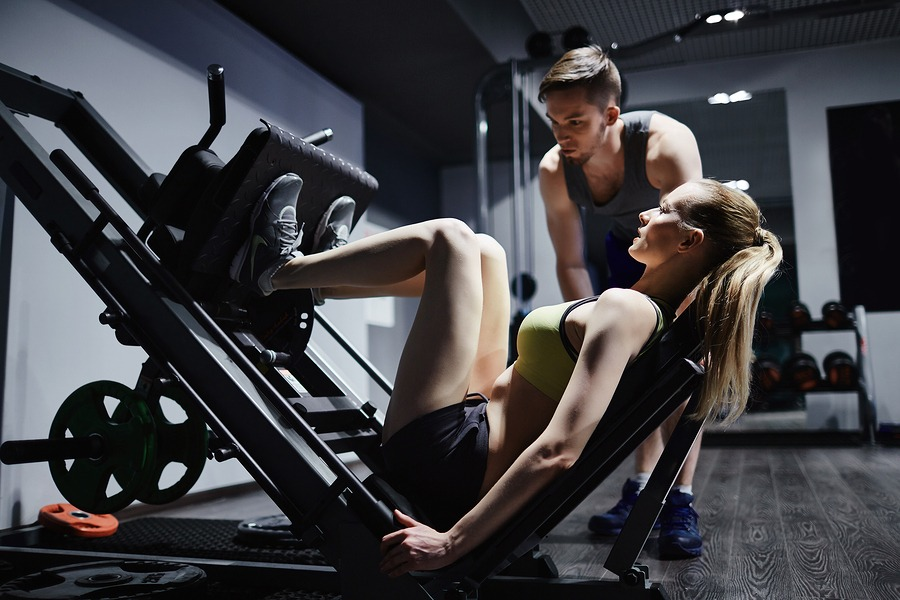 Active woman doing exercise for legs on special equipment with t